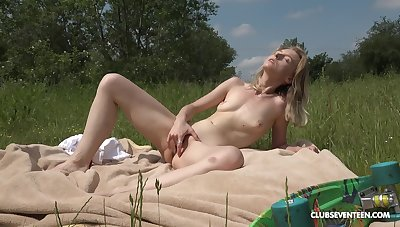 Blonde girl feels insolent in the outdoors fingering her cunt