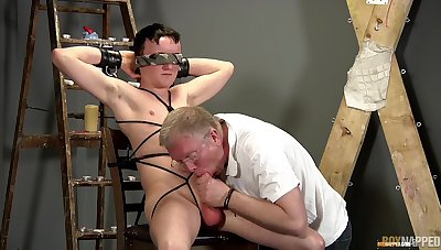 Old scrounger sucks twink's dick during their BDSM gay shtick